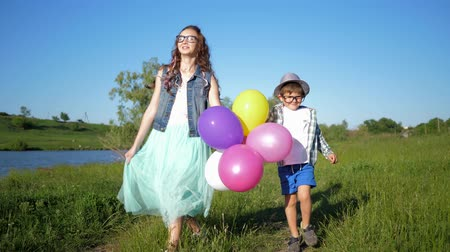 petite : happy children in glasses with colored balloons in hands have fun on green lawn near lough on vacation