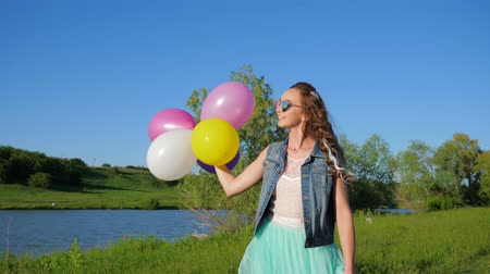 loch : smiling teenage girl in sunglasses with balloons in hands walking on river bank to green grass on warm spring day