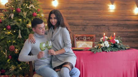 шампанское : holiday emotions, girl sits on arms of spouse and kisses him with green glasses in hands on the background of festive table and fir tree
