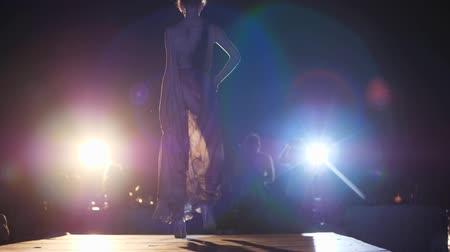 floodlight : fashion catwalk, model girl in chiffon dress and stylish shoes goes down podium in bright spotlights at night