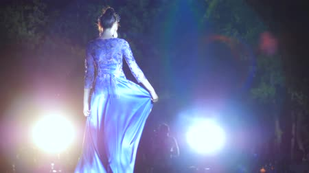 pist : defile professional model in luxurious evening dress on catwalk in lighting spotlights on fashion show