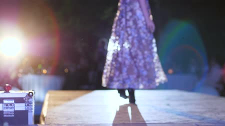 searchlight : fashion evening, model makes defile into long luxurious dress and high-heeled shoes on podium in unfocused in spotlight lighting