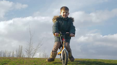 petite : happy childhood, small boy is riding bicycle without pedals from hill on green grass on nature against sky