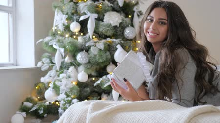 kar taneleri : young woman with gift in hands lies at sofa and looks at camera on background green christmas tree with toys Stok Video
