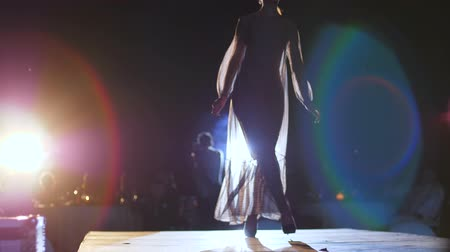 high heeled shoe : fashion week, Catwalk models in elegant long dresses on high heels walk along podium in bright searchlight lighting Stock Footage