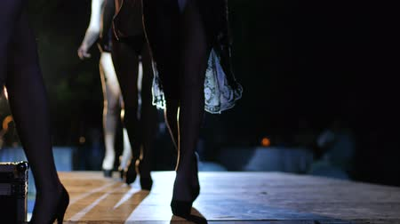 high heeled shoe : slender legs of models in black shoes on high heels go in row along catwalk at fashion show of underwear
