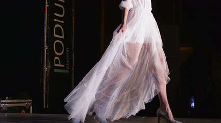 podium : Kherson, Ukraine 02 June 2018: Defile show, beautiful girl into fashionable white dress walking along catwalk in searchlight lighting in Kherson, 02 June 2018.