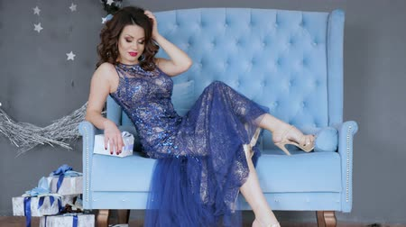 high heels : sexy brunette posing at camera in evening long dress on blue couch beside gift boxes in studio