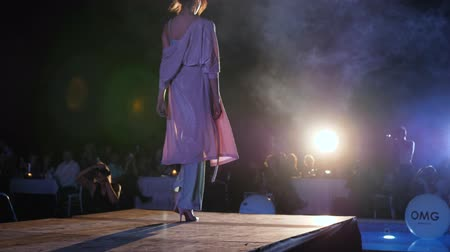 high heeled shoe : Kherson, Ukraine 02 June 2018: presentation of new collection designer clothes, woman model in fashionable shiny suit and high heels walking down catwalk in Kherson, 02 June 2018.
