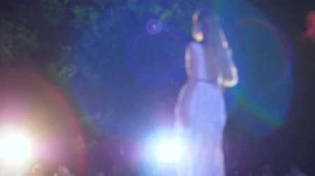 podium : Kherson, Ukraine 02 June 2018: professional model into white evening dress walking along catwalk at illumination of spotlights in unfocused in Kherson, 02 June 2018. Stock Footage