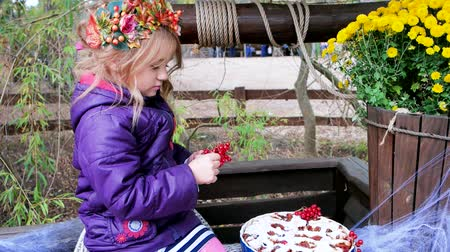 baked pumpkin : girl decorating baked pie with red berries, halloween preparation, wearing wreath of leaves and viburnum