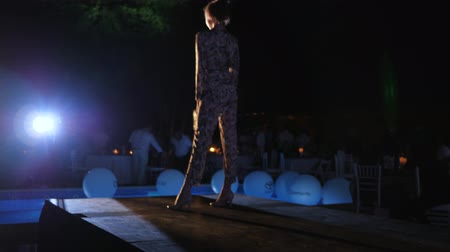 floodlight : Kherson, Ukraine 02 June 2018: smiling model into elegant suit walks on catwalk in fashion evening in Kherson, 02 June 2018.