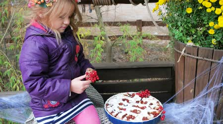 baked pumpkin : little girl decorating pie with virburnum, halloween preparation, wearing wreath of leaves and viburnum