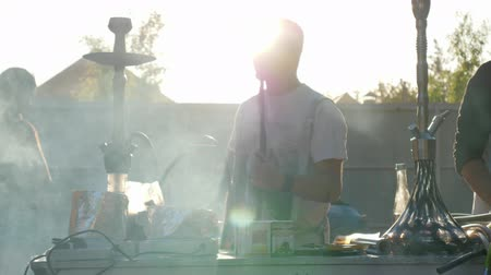 saborear : Kherson, Ukraine 02 June 2018: smoking male with hookah emits thick haze from mouth on open air in sun rays in Kherson, 02 June 2018.
