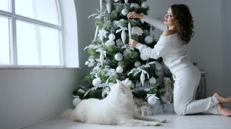 hound : celebration atmosphere, happy young woman decorates xmas tree in white tones at home