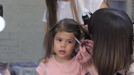 fonat : professional visagiste with hairdresser do Stylish makeup and hairstyle for child in beauty salon close-up