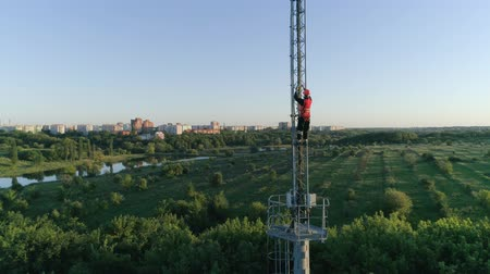work at height : dangerous job, drone view on man in hard hat get down from the radio telecommunication tower with the help of belay on background of beautiful landscape Stock Footage