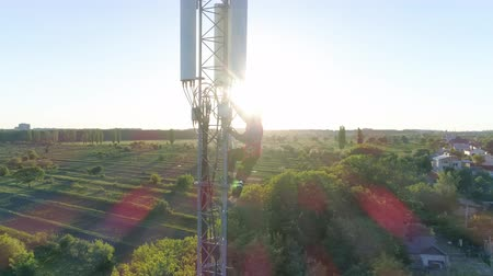 telekomünikasyon : drone view of cellular antenna, radio telecommunication tower with worker on background of beautiful city landscape in sunlight