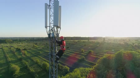 work at height : engineer in a safety vest and hard hat climbs high on cellular antenna, drone view of telecommunication tower