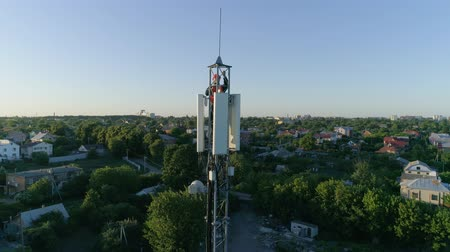 película de filme : technical worker on top of cellular antenna show thumbs up, aerial shot of telecommunication tower