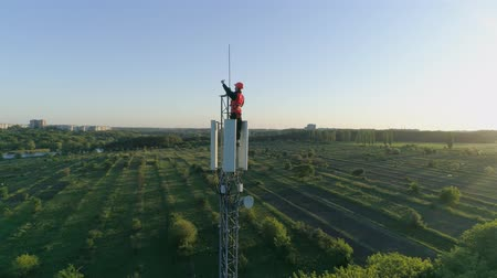 work at height : happy man at work on top of cellular antenna, technician on radio telecommunication tower raises hand with thumb-up on background of blue sky Stock Footage