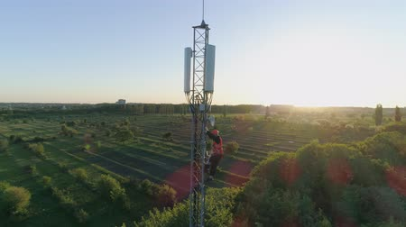 duro : worker get down from the radio telecommunication tower with the help of belay on background of beautiful landscape