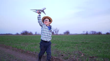 aberto : happy weekend, child holds a toy plane and runs along the green field