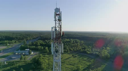 telecomunicação : technician worker servicing cellular antenna, drone view of telecommunication system tower on blue sky background
