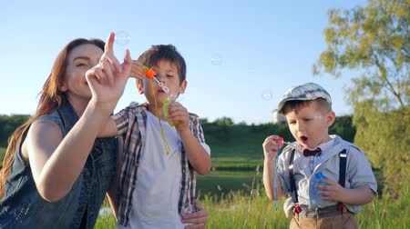 petite : children relationships, cute little boys with teenage girl blowing soap bubbles on meadow close-up