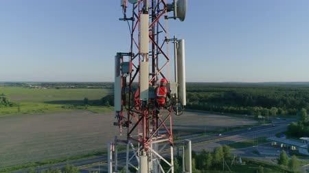 telephone tower : High-Altitude Work, technician serves the antennas of mobile telephony, internet, television on the background of the gray sky