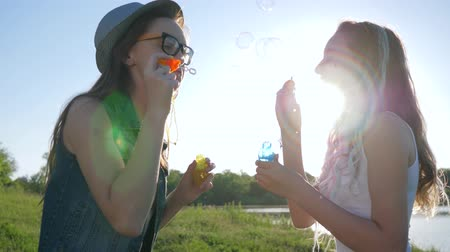 loch : emotional girlfriends make soap bubbles and laugh outdoors near river against sky in bright sunlight