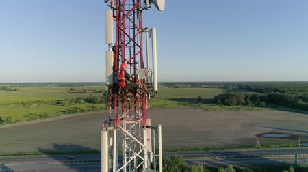 telephone tower : Cell phone telecommunication tower with worker which holds the tablet in hand programming antennas