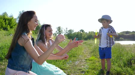 petite : happy children life, nice boy with hat blows soap bubbles at girls teenagers sitting on green grass