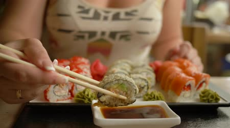 mastigação : traditional Japanese cuisine, hungry woman eating sushi with soy sauce using sticks in restaurant close-up