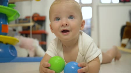 petite : beautiful baby boy with colored plastic balls lying on floor in game room close-up