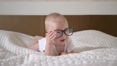 do interior : babyhood, portrait of cute little child boy with big blue eyes in glasses lies on the bed close up