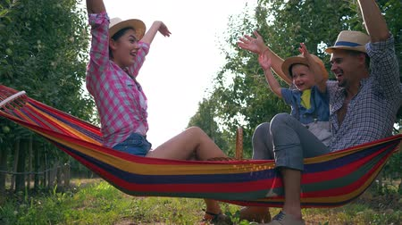 hamak : holiday home, happy parents with child on hammock in a apple garden have funs and enjoying nature in straw hats at warm summer day