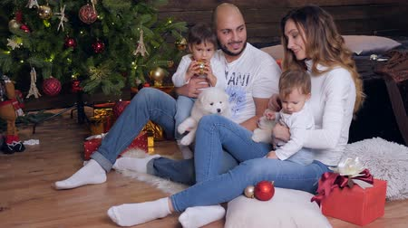 рождественская елка : new year parents and kids sit on floor with puppies, husband and wife looking at each other with great love on background illuminated christmas tree