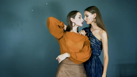 modelo de moda : models show new clothes, famous ladies with bright make-up and with earrings in ears close-up together posing on camera on dark blue background