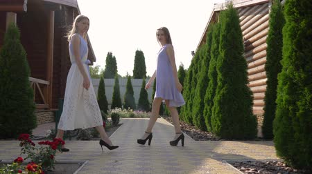 модный : models defile outdoors, girls in dresses are walking in the garden and look at camera