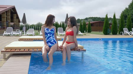 bordas : summer time, relaxing girls are sitting on the edge of the pool at a hot sunny day on luxury vacation Stock Footage