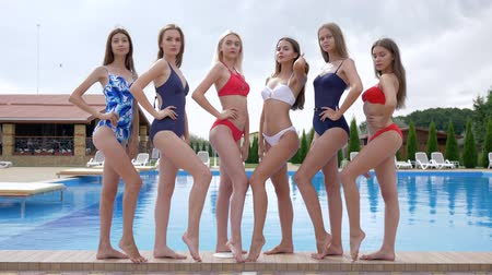 young bird : young sexy girls in swimsuits poses on the edge of poolside barefoot at a hot summer day