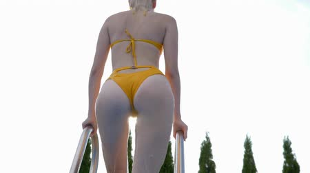 comes : sexy girl in a yellow swimsuit comes out of the blue swimming pool and walking along the summer terrace