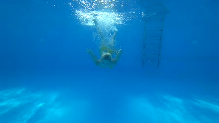 cintilante : active summer holidays, view from underneath of blonde girl in yellow swimsuit underwater in pool with bright light reflecting against the surface of the water Stock Footage