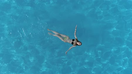 delgado : young woman floats lying on a water surface in crystal clear pool at summer, aerial shooting from flying drone Vídeos