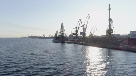 újrahasznosítható : aerial view of cargo port with cranes in backlight, large ship in industrial harbor