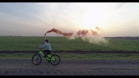 barevný : child learns to ride a bike, little boy with a colorful smoke bomb on a country road Dostupné videozáznamy