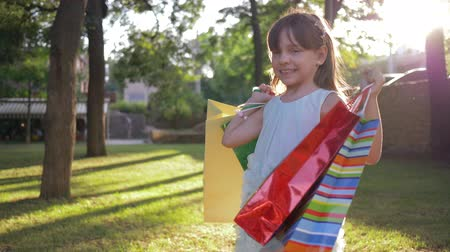 rejoices : portrait of shopper child with lots of purchases from expensive boutiques stands at park and smiles on warm sunny day