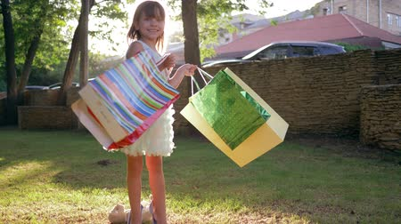 rejoices : shopper child of rich parents waving many packet into hands after purchases in expensive boutiques on nature in backlight Stock Footage