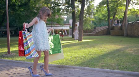 high heeled shoe : children shopping, trendy little girl in high heeled shoes with lot paper bags in hands walking on street